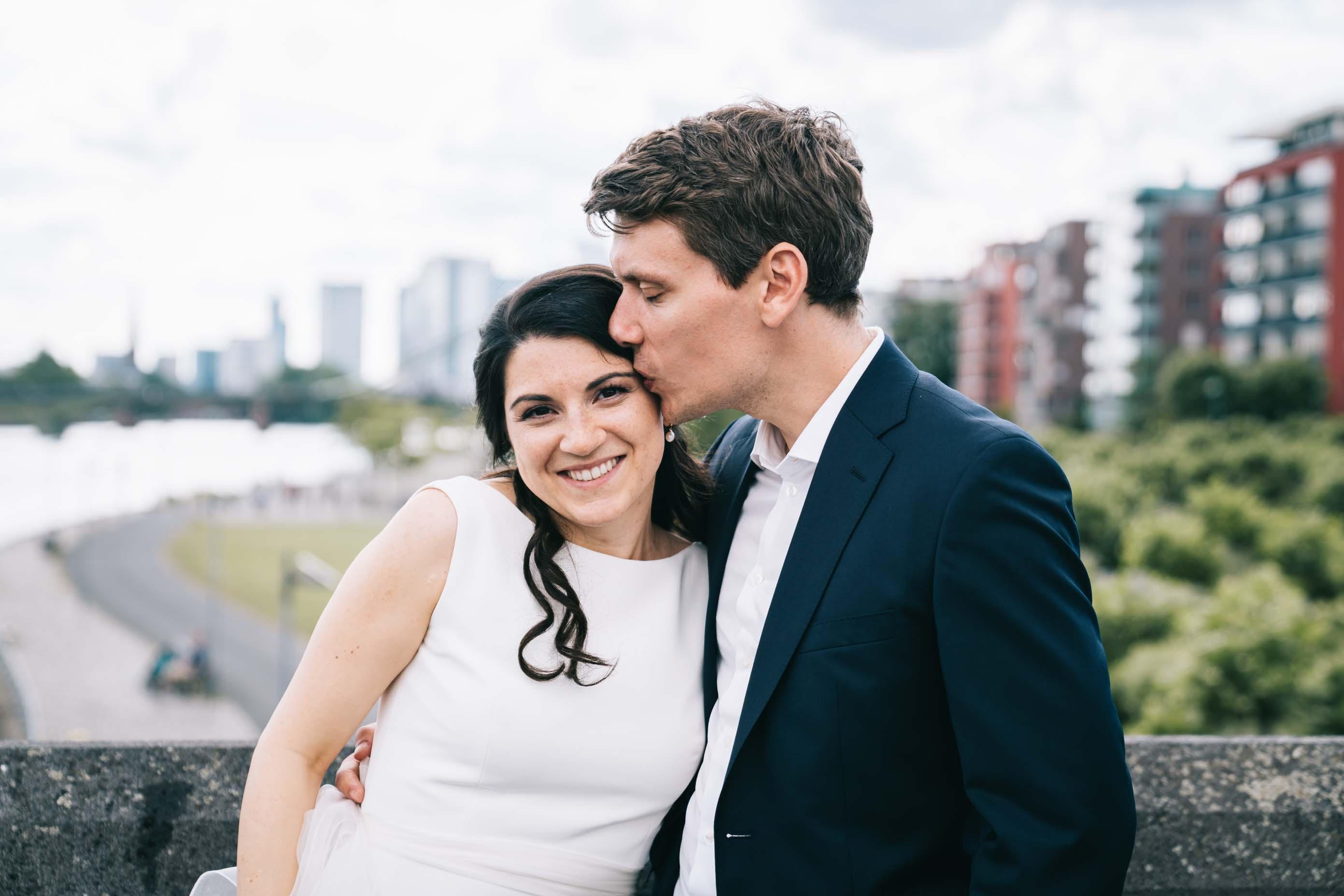 Der Bräutigam küsst seine Braut auf die Stirn.