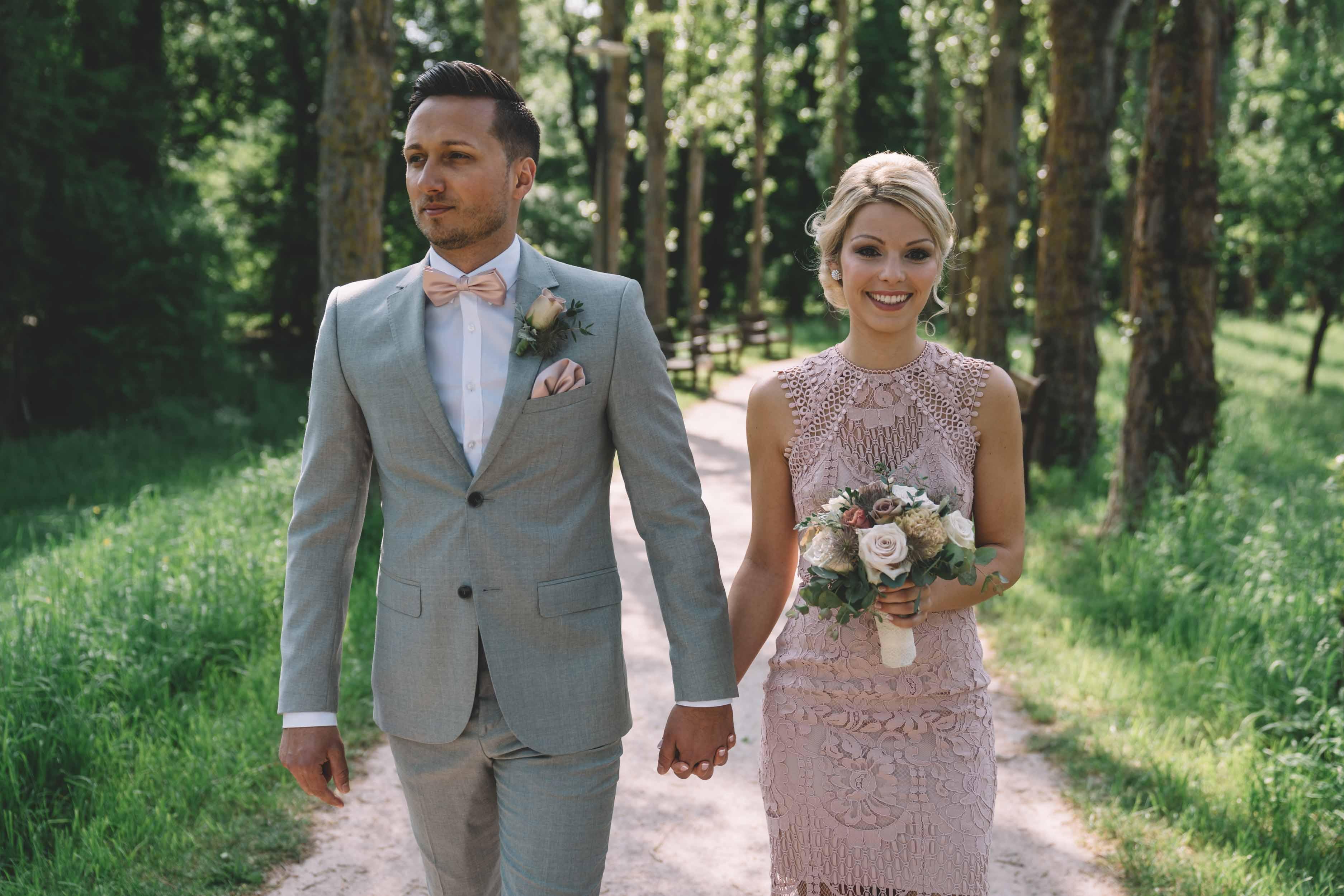 Das Brautpaar läuft Hand in Hand im Park entlang.
