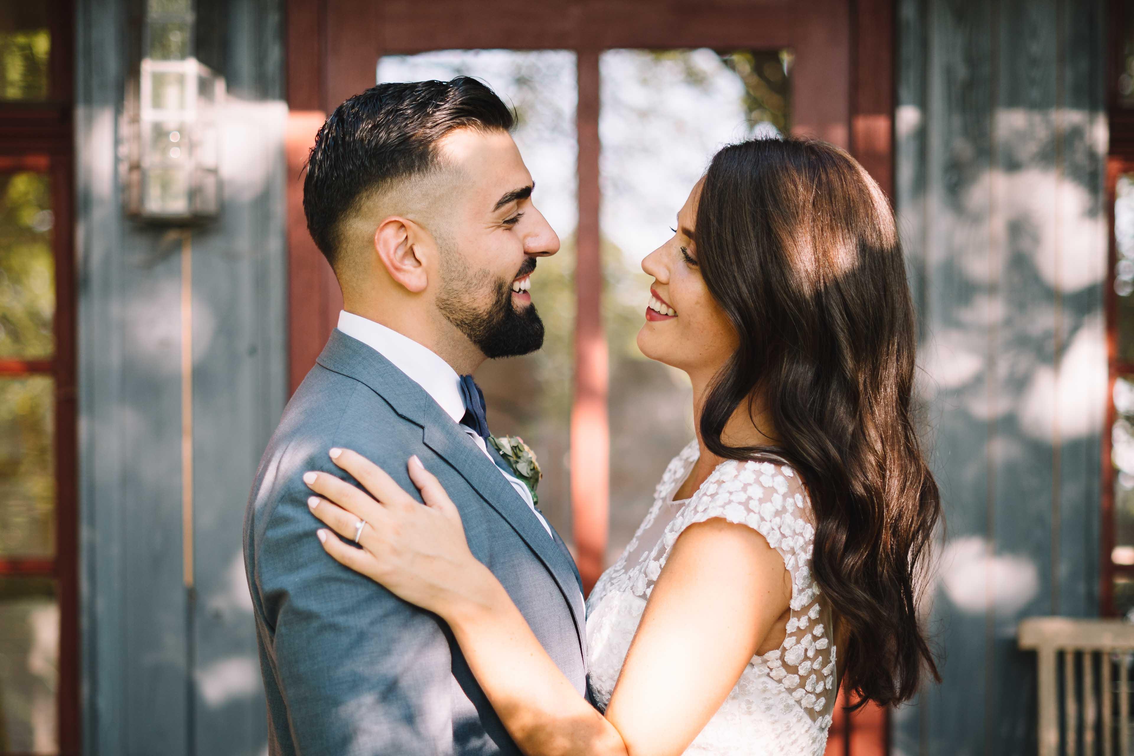 Das Brautpaar posiert vor einer alten Gartenlaube.