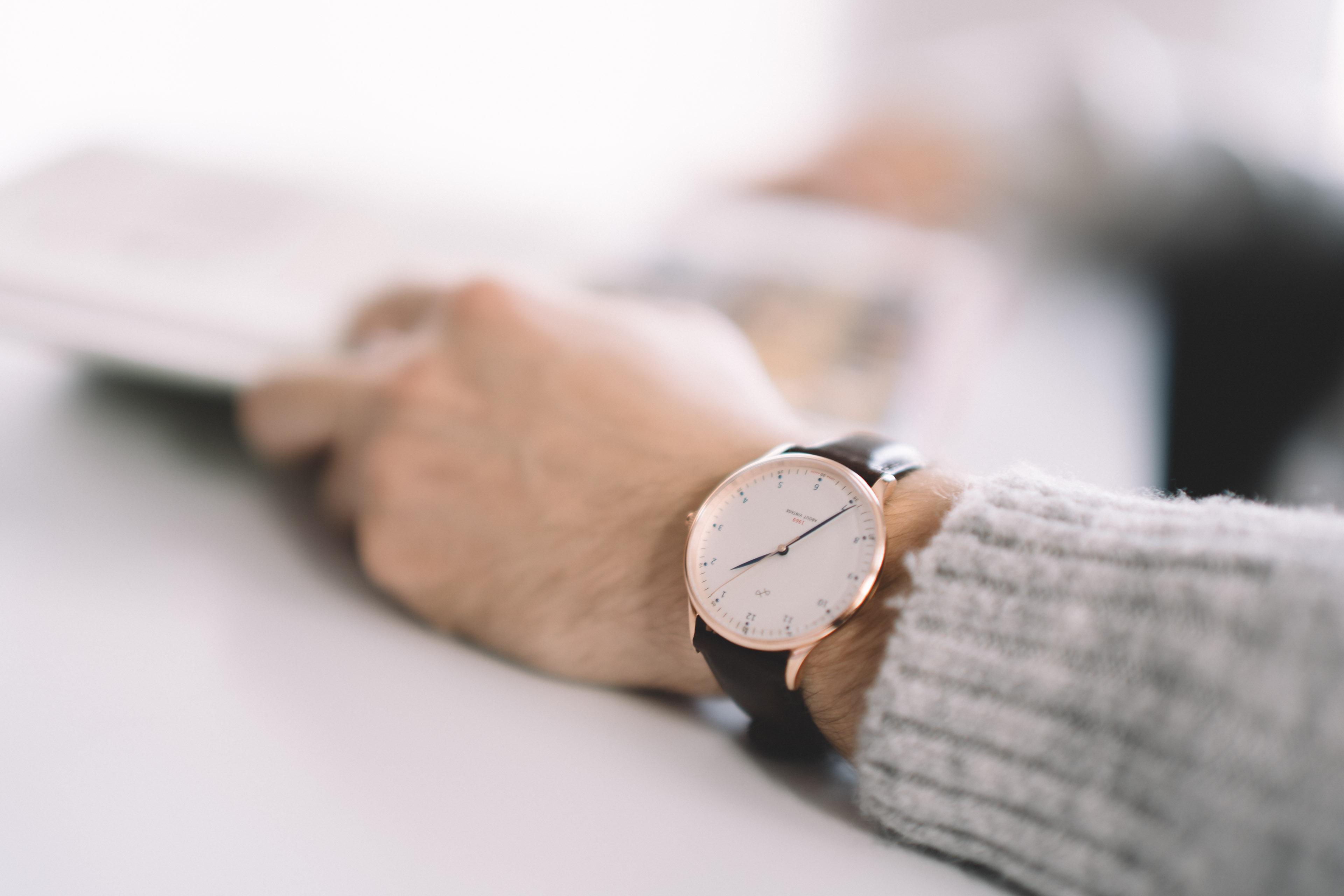 Ein Mann liest eine Zeitung und präsentiert seine Armbanduhr.