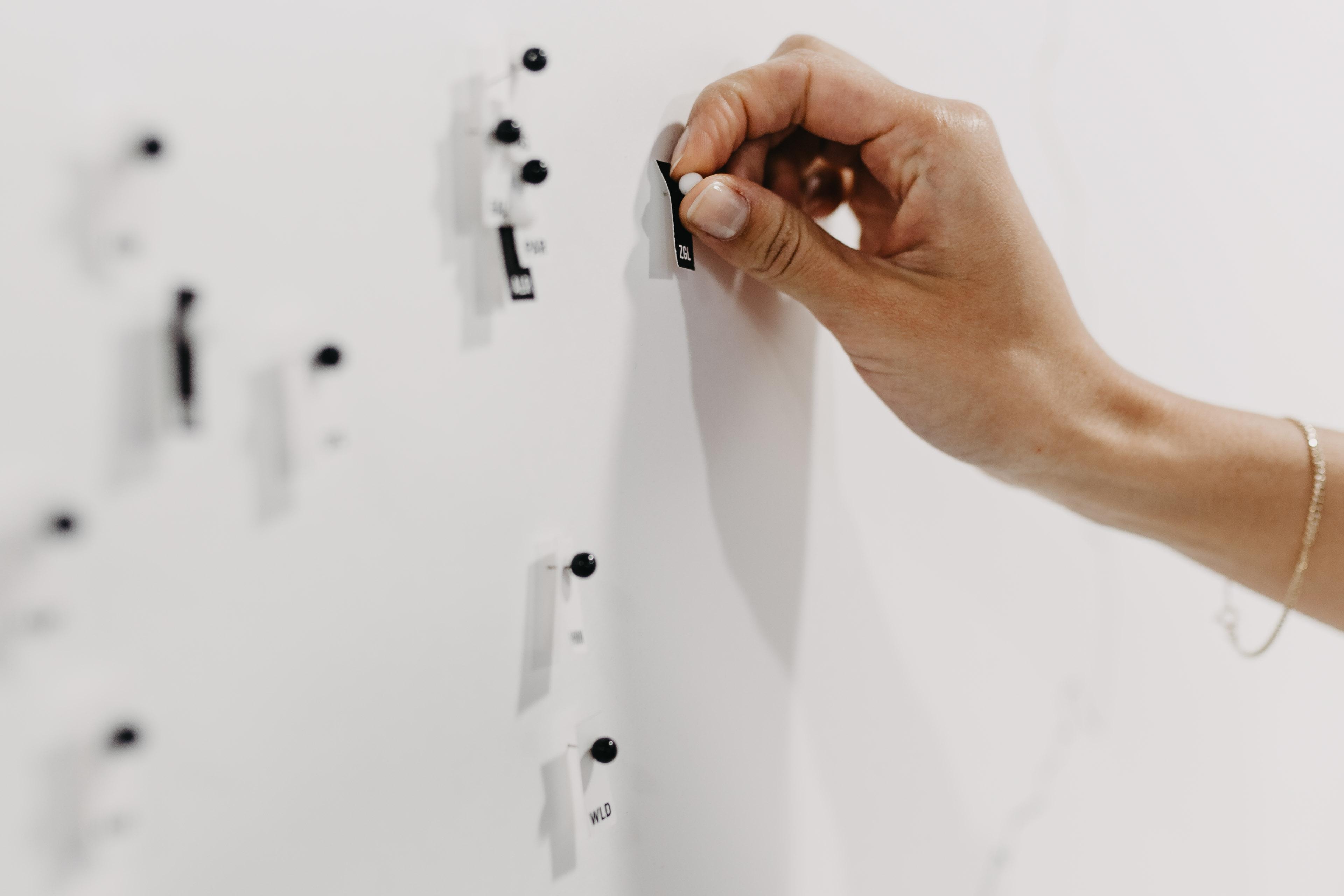 Eine Hand pinnt Stecknadeln an die Wand.