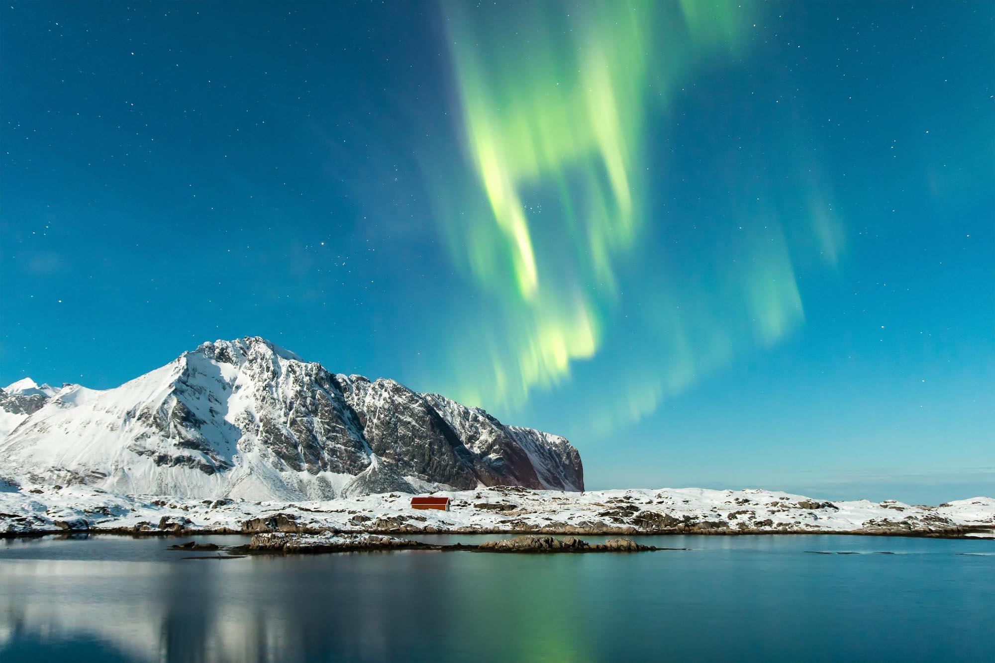 Polarlichter flackern über einer kleinen Insel in Norwegen.