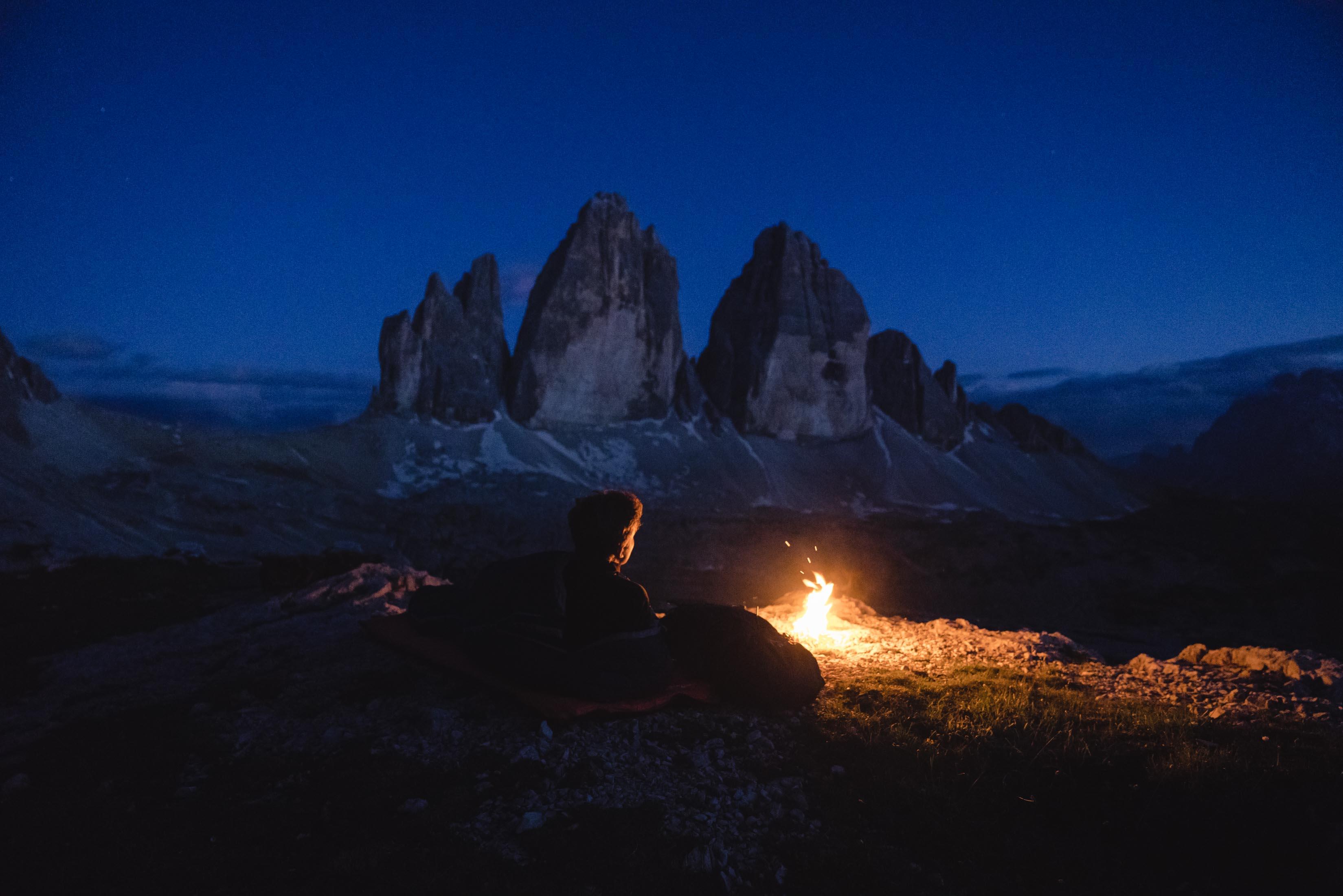 Ein Lagerfeuer vor den Drei Zinnen bei Nacht.