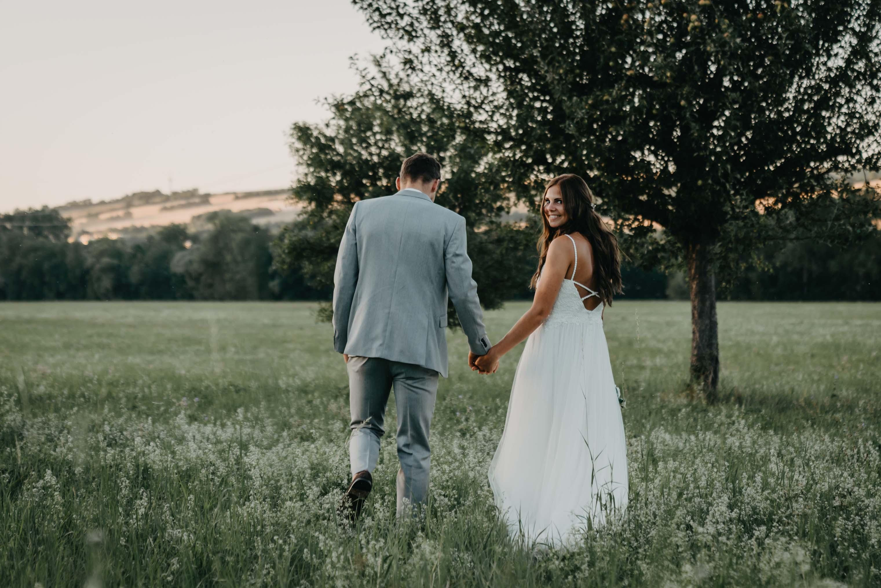 Das Brautpaar geht Hand in Hand über eine weite Wiese.