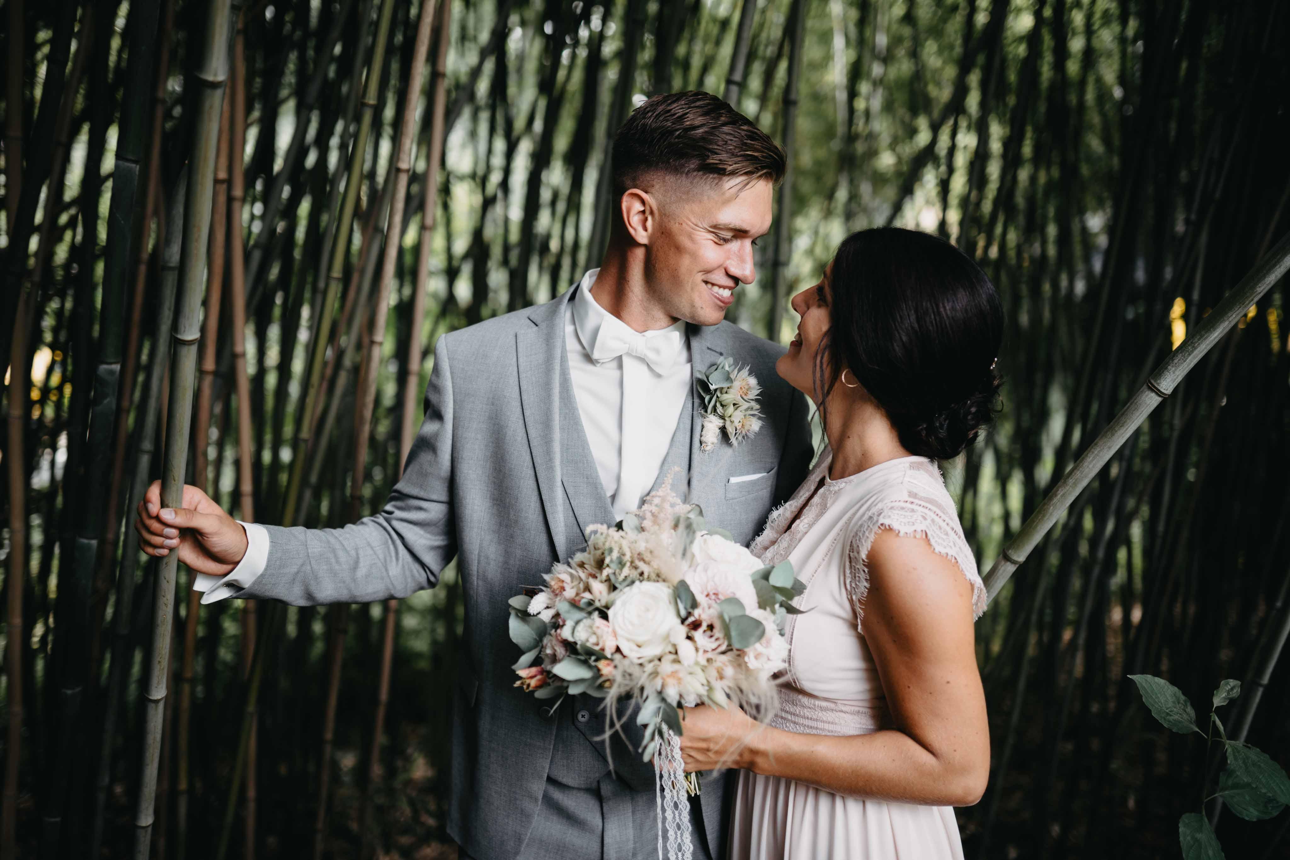 Das Brautpaar steht eng beieinander und ist von Pflanzen umringt.
