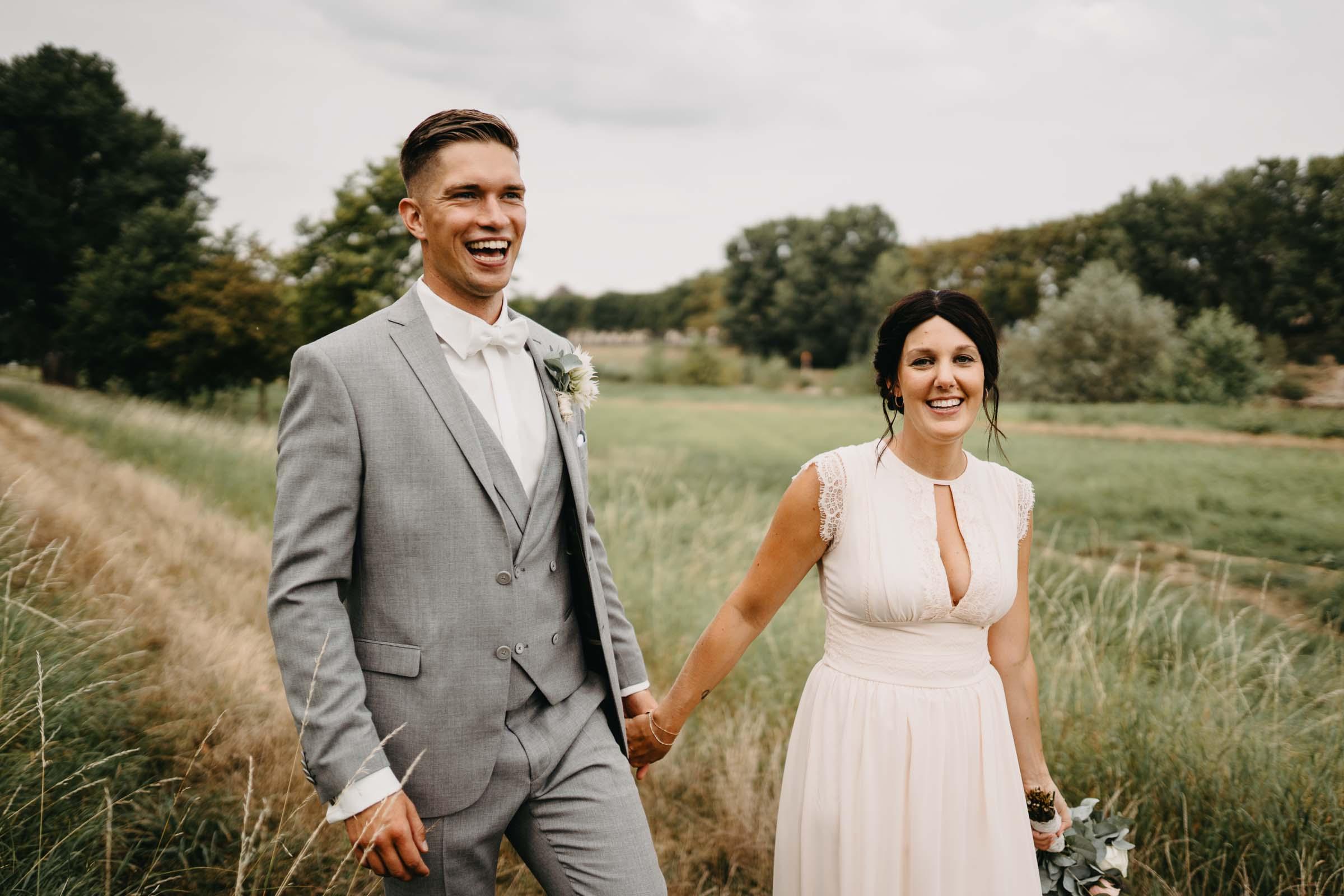 Das Brautpaar läuft Hand in Hand auf einem Feldweg.