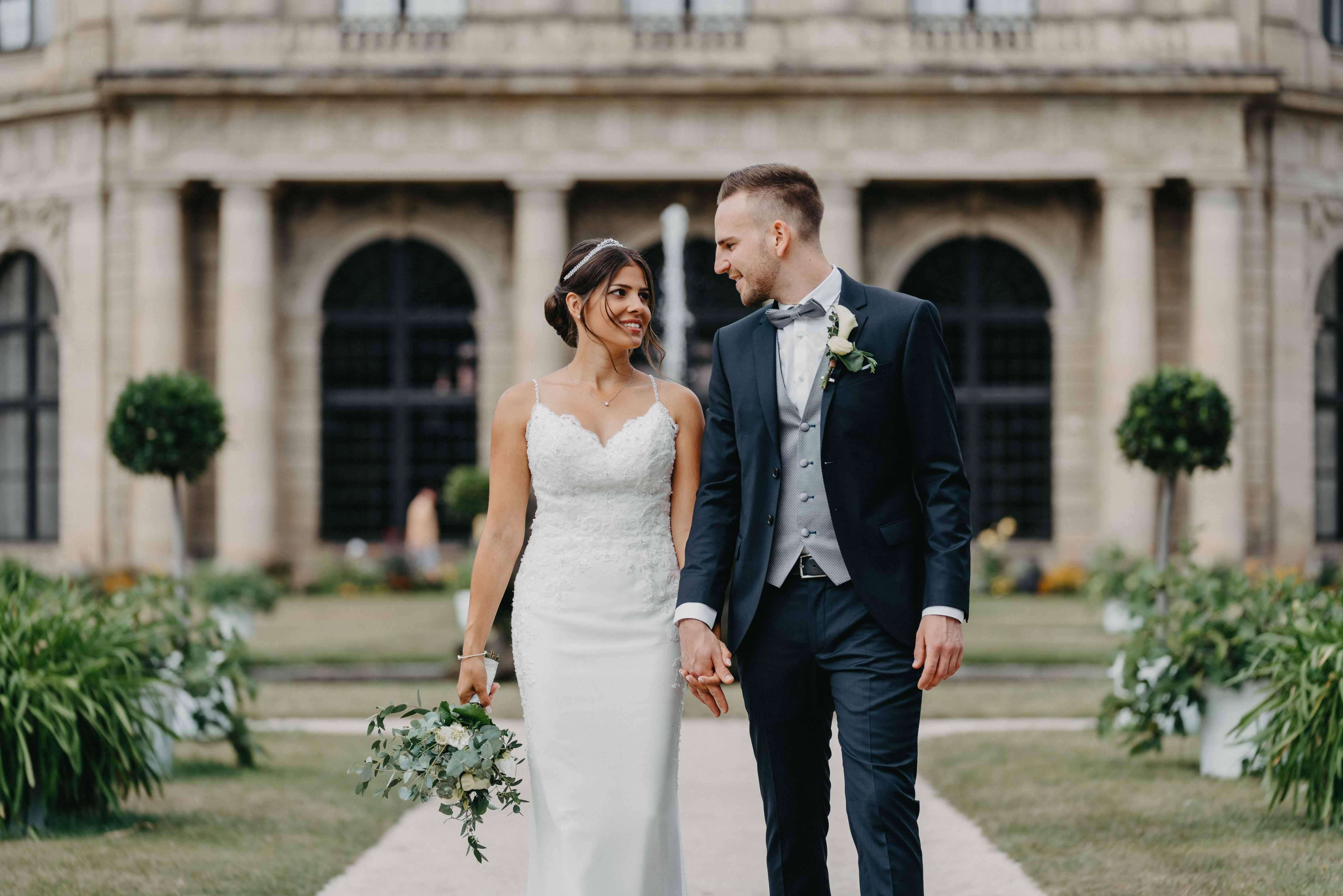 Das Brautpaar läuft zusammen im Garten.