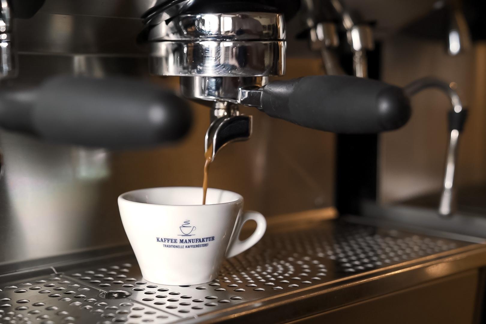 Kaffee läuft aus der Maschine in eine weiße Tasse.