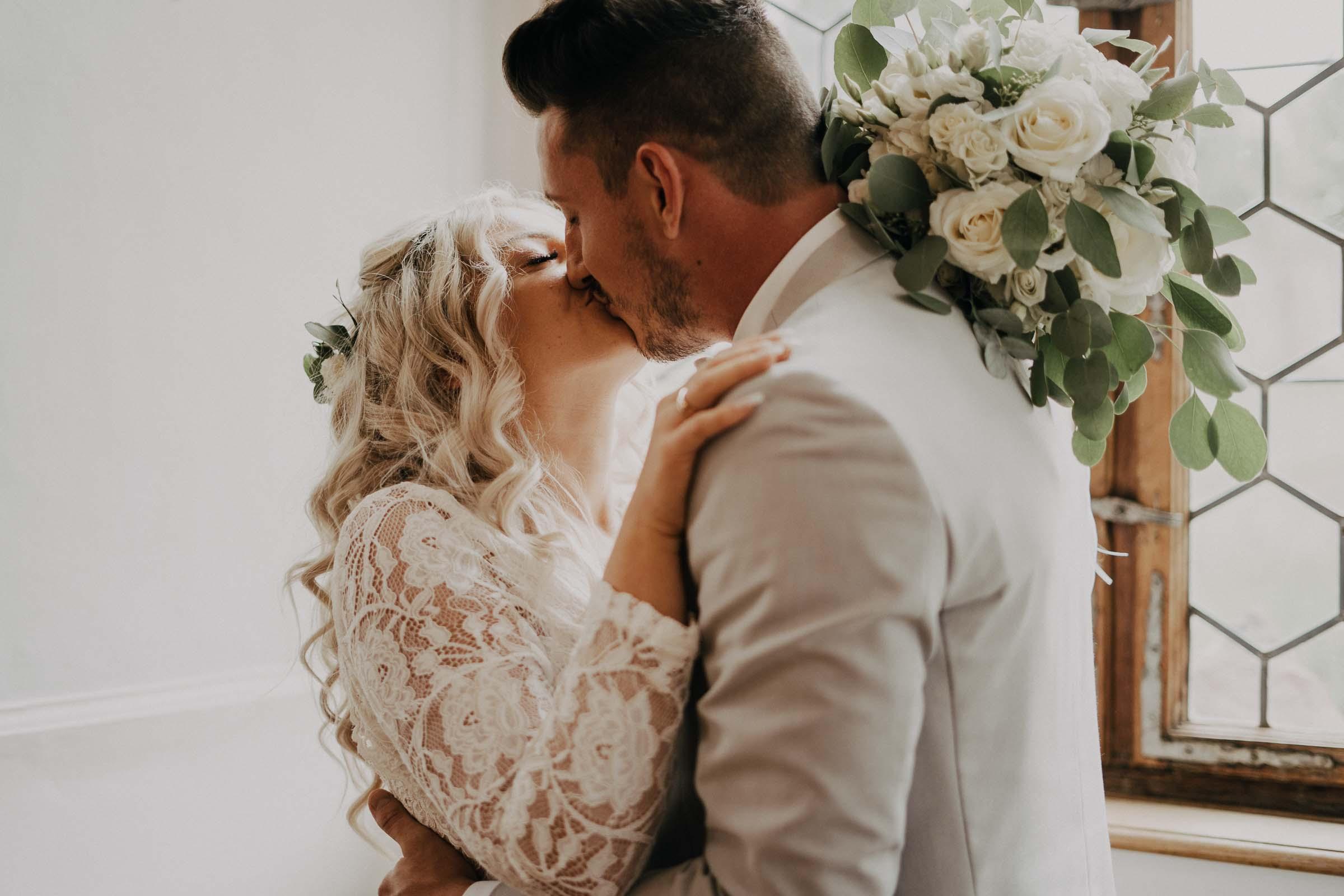 Das Brautpaar küsst sich vor einem Fenster.