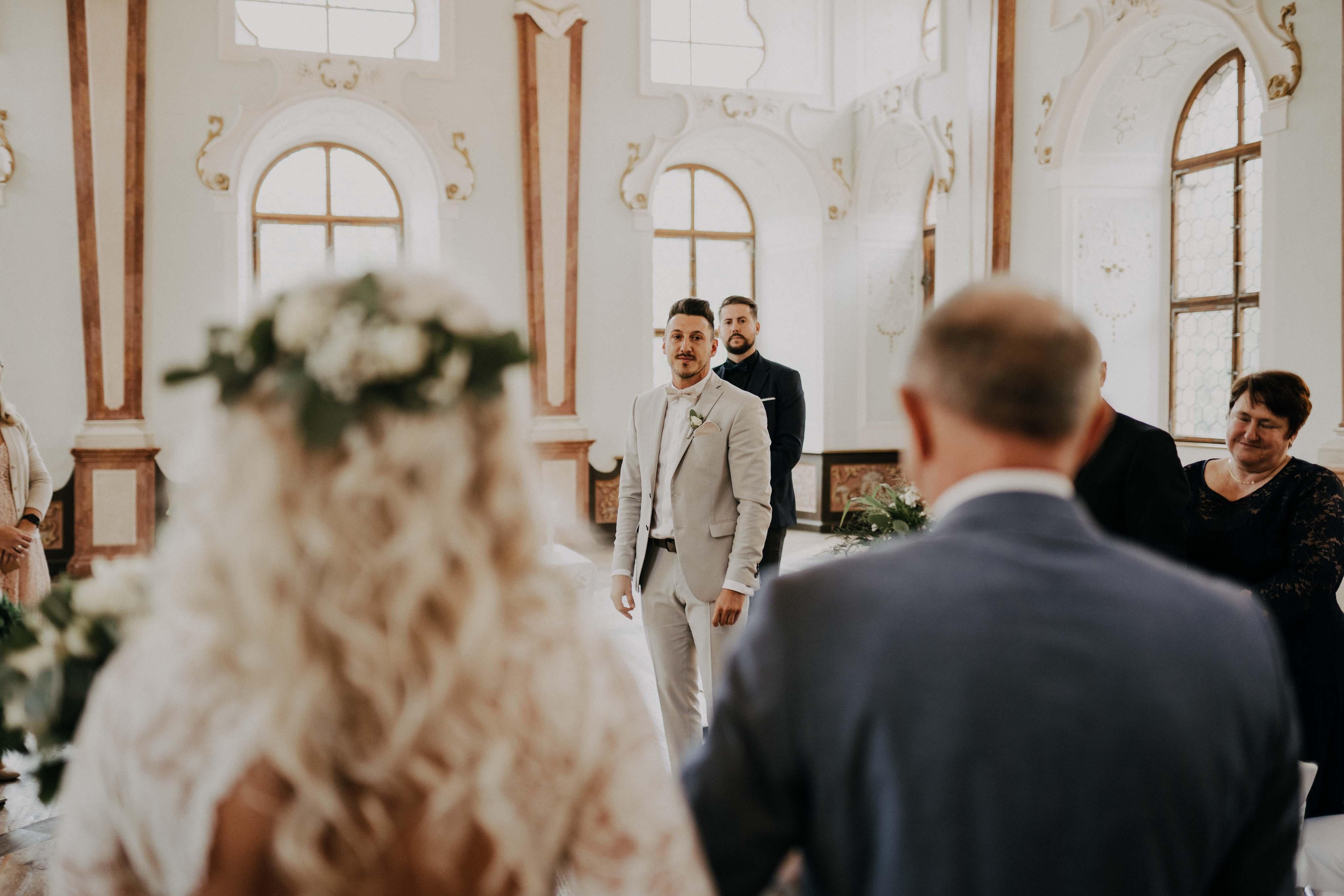 Der Bräutigam erblickt seine Braut, die von ihrem Vater zum Altar geführt wird.