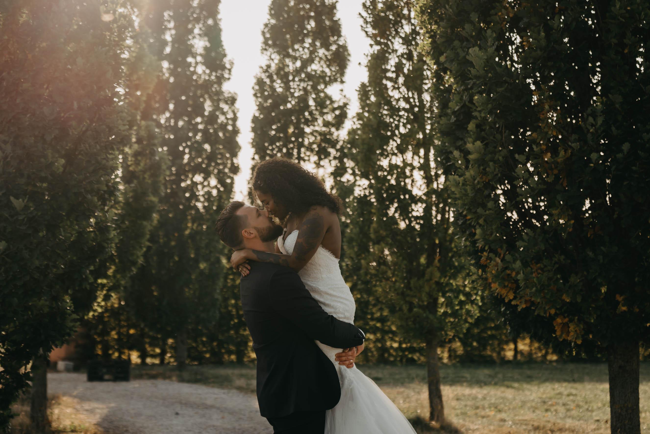 Der Bräutigam hebt seine Braut in der tief stehenden Sonne hoch.