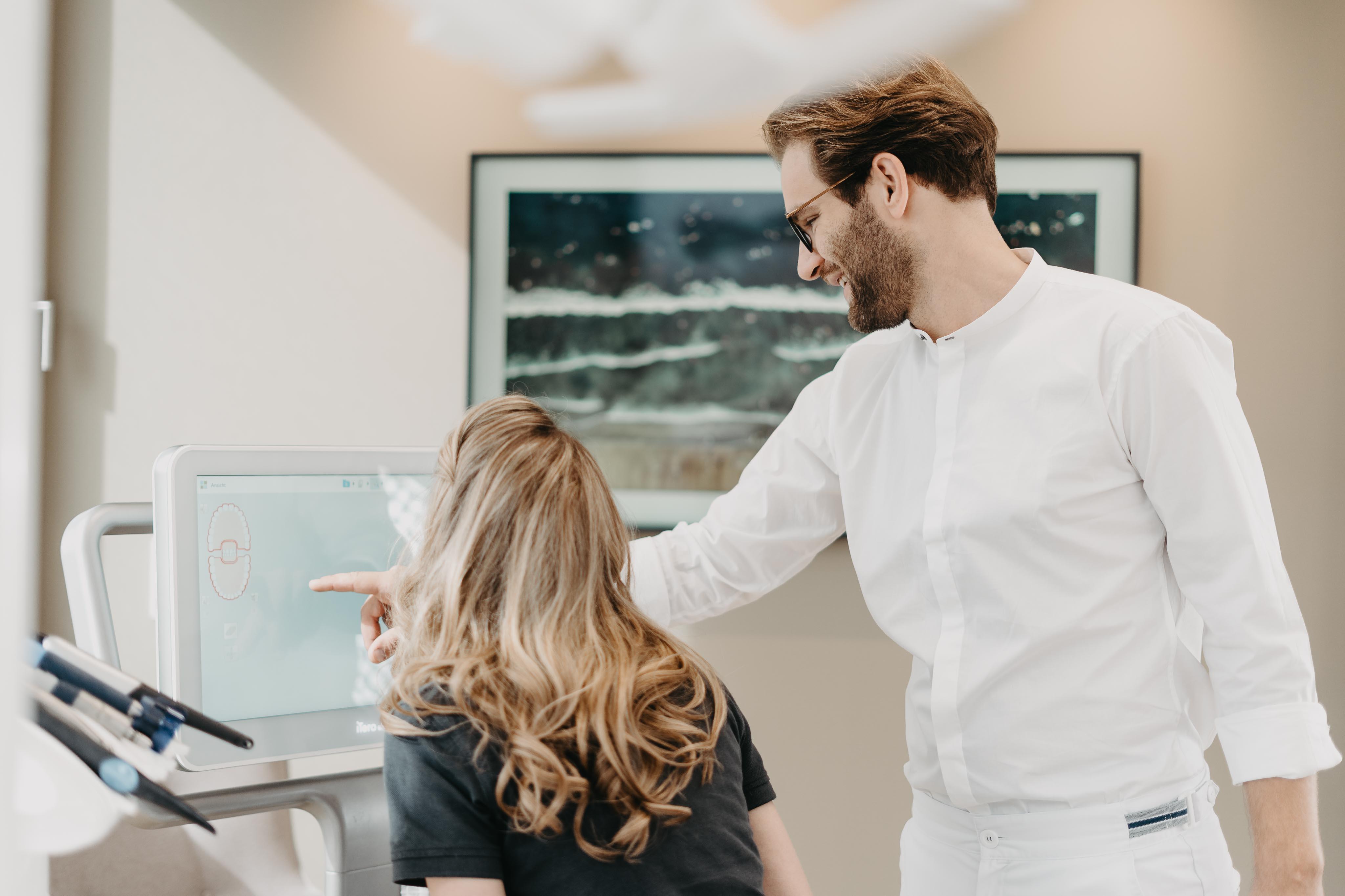 Ein Mann zeigt einer Frau etwas auf einem Monitor.