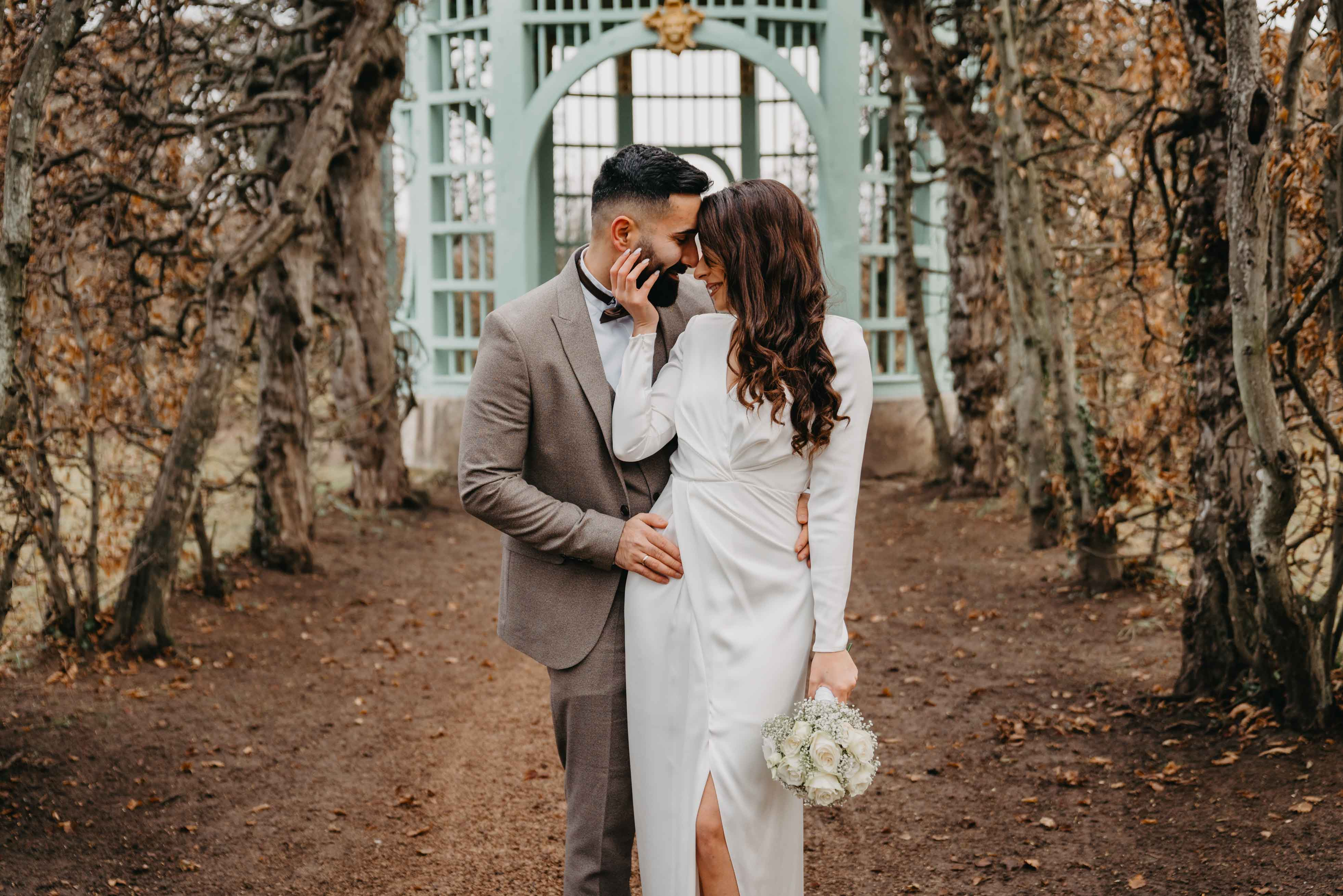 Der Bräutigam umarmt seine Braut von hinten.