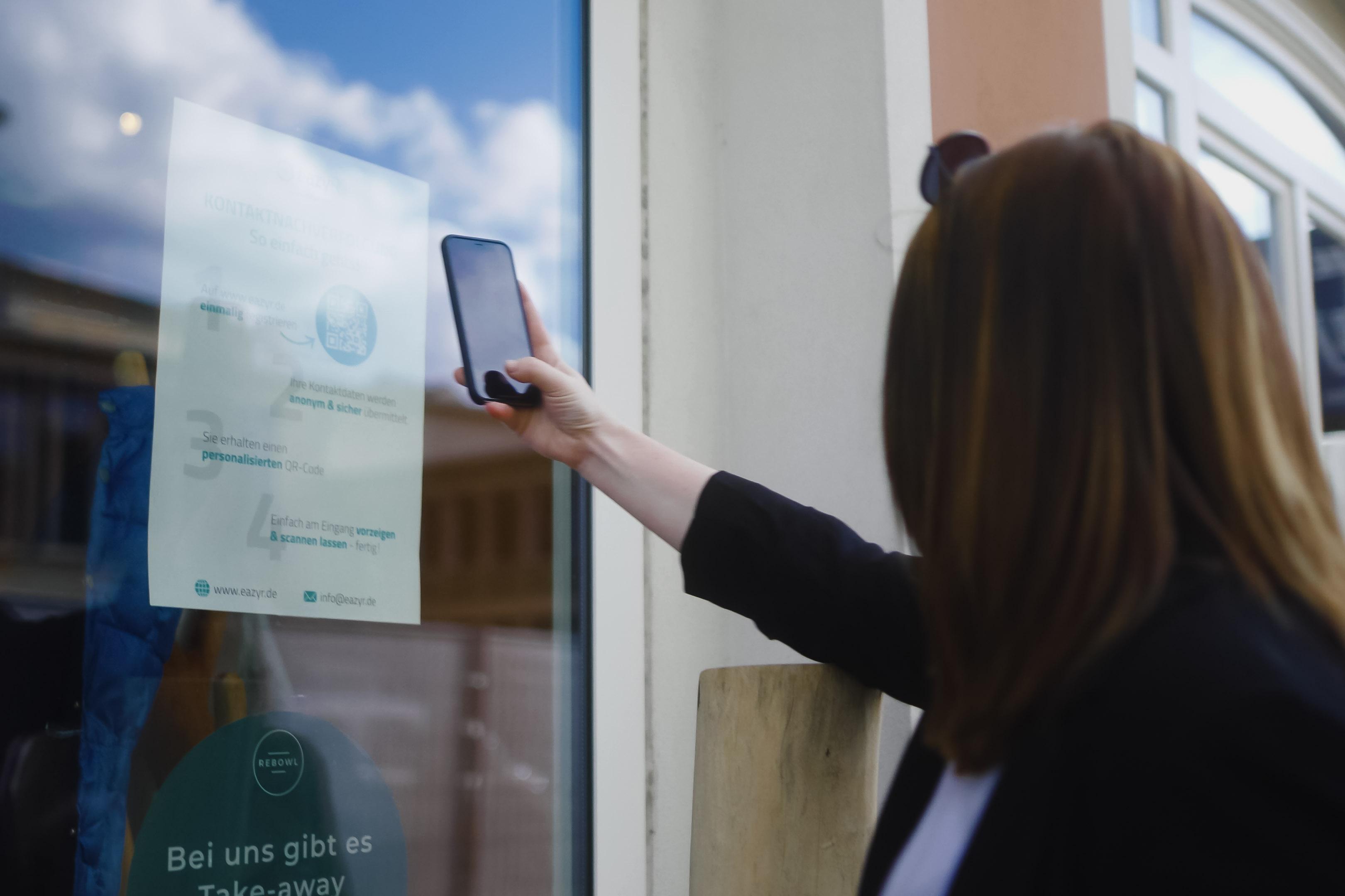 Eine Frau scannt mit ihrem Handy einen QR Code.