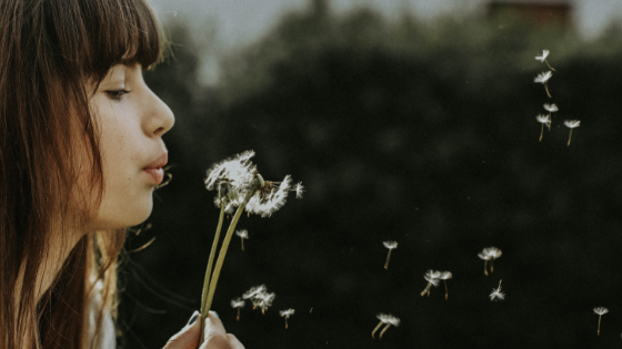 Woman blowing dandelion.