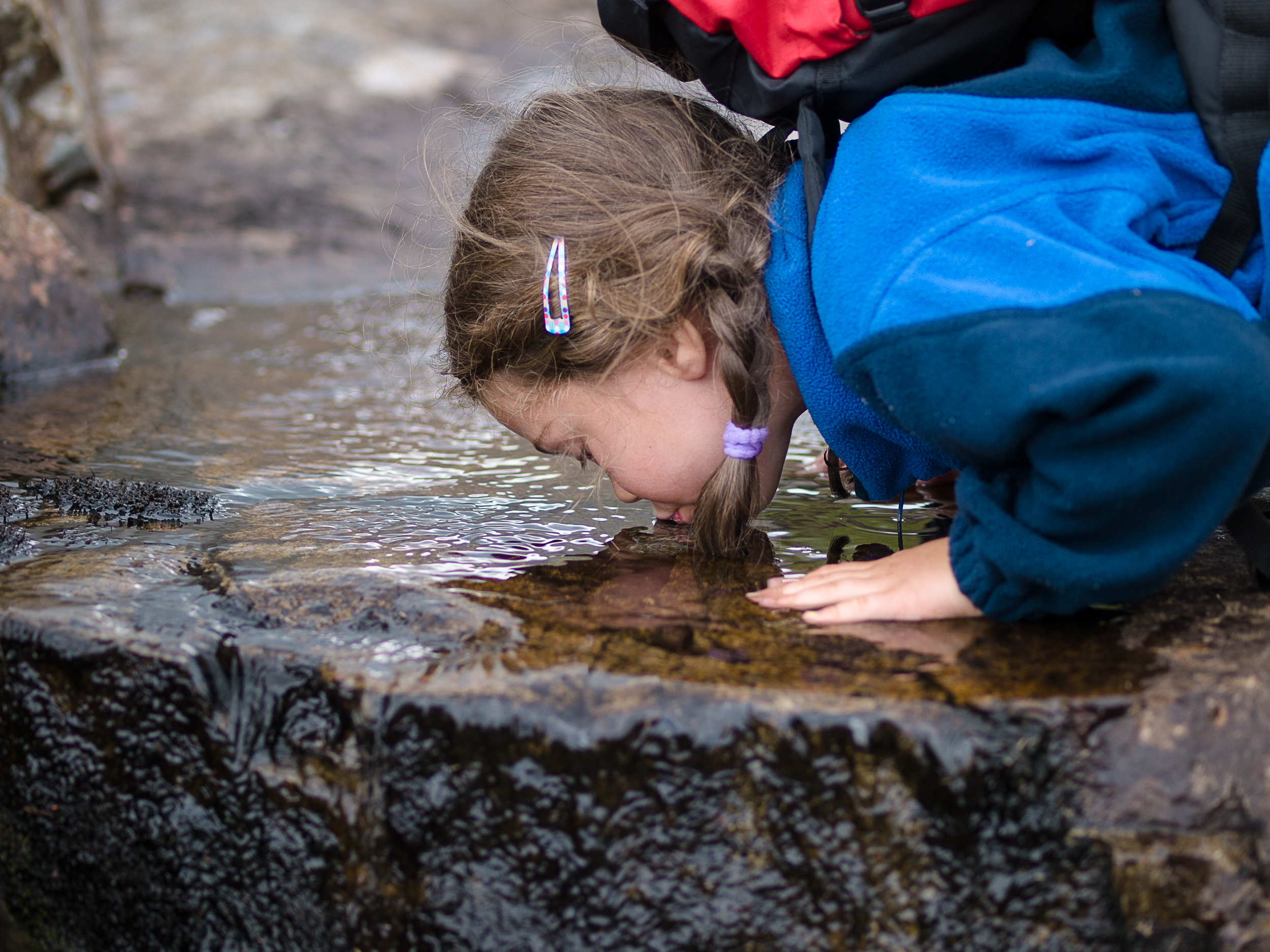 Girl drinking water from the stream