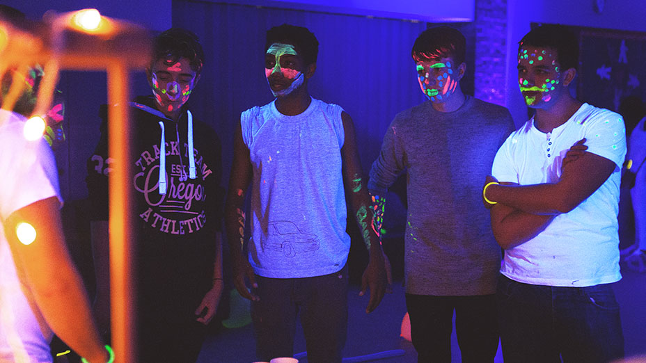 Group of young people wearing light t-shirts and various patterns of neon facepaint in a darkly lit room