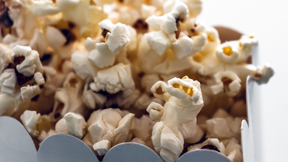 A close-up image of overflowing popcorn in a box
