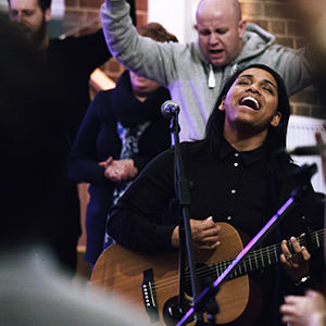 Musician with a guitar leading a group in worship during Encounter at regeneration Church