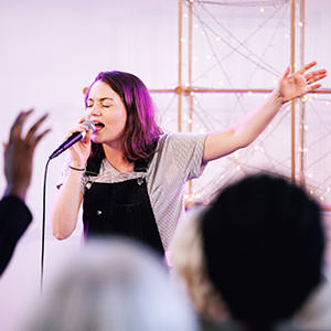A singer with her arm aloft in front of a fairy light cross leading people in worship at a regeneration Church service