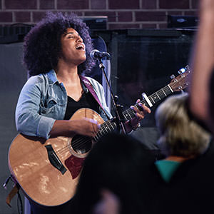 Musician leading worship with guitar during a Half Four service at regeneration Church