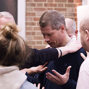 A group of people laying hands in prayer on the shoulder of a man, who has his hands open, during Fuel at regeneration Church