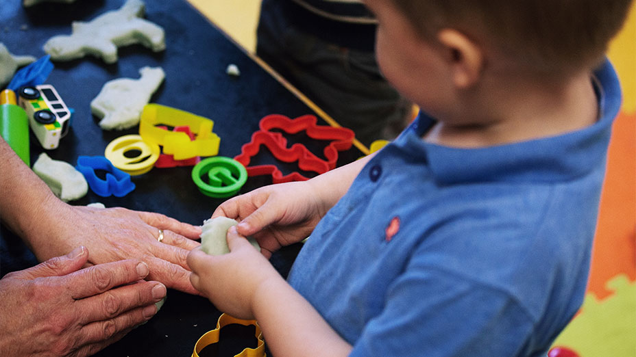 A toddler shaping with Playdoh with various shape cutters visible at Little Paws