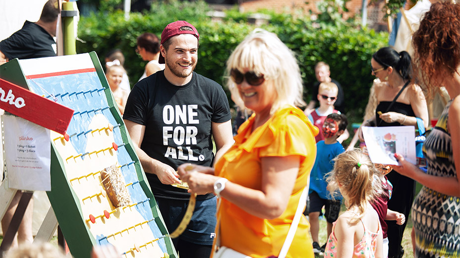A woman in an orange blouse standing outside and smiling at a Plinko board in the foreground, with a group of other adults and children in the background