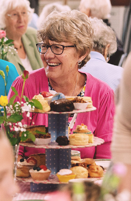 A group of seniors enjoying coffee and cake around tables at an Afternoon Tea