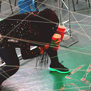 Young person trying to navigate through a spider's web game, holding cups of water