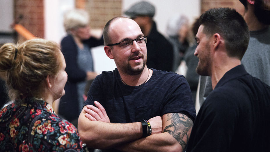 Three adults enjoying conversation in the foreground with other people talking in the background during a meet and greet time