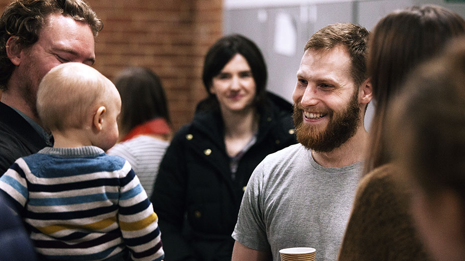 Man holding a coffee smiling at a child who is being held by their father during the Welcome Lounge at regeneration Church