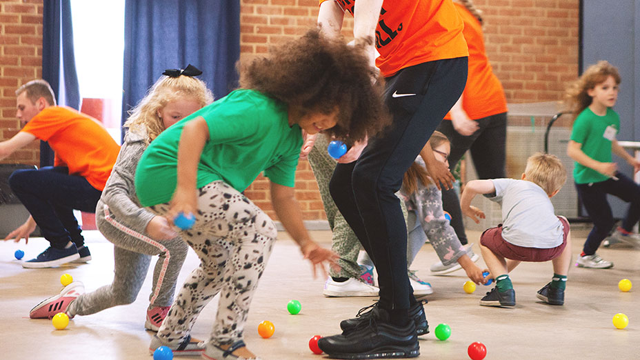Children trying to collect multi-coloured balls on the floor as part of a game at a Holiday Club