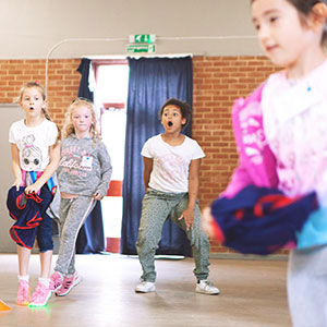Children racing around cones as part of a game at a Holiday Club