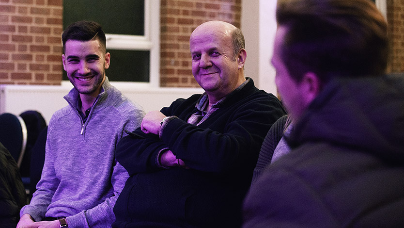 Three men laughing together during discussion at Charcoal at regeneration Church
