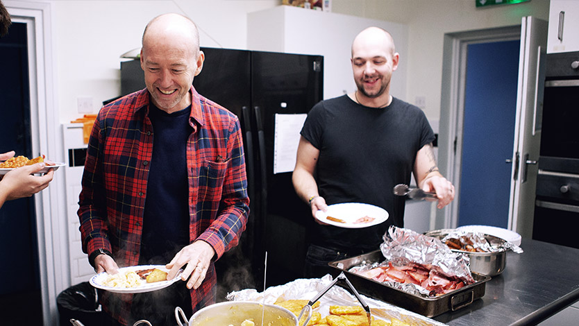 Two men plating up sausages, hash browns and bacon at a Cobalt Breakfast