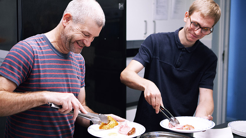 Two men holding plates and helping themselves in front of containers of sausages, bacon, eggs, hash browns and mushrooms during a Cobalt Breakfast