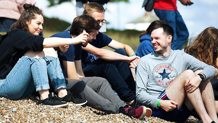 A group of four adults laughing on a sunny stone beach in Sizewell