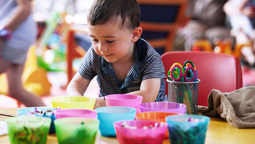 Toddler looking at colourful pots and craft items during Little Paws