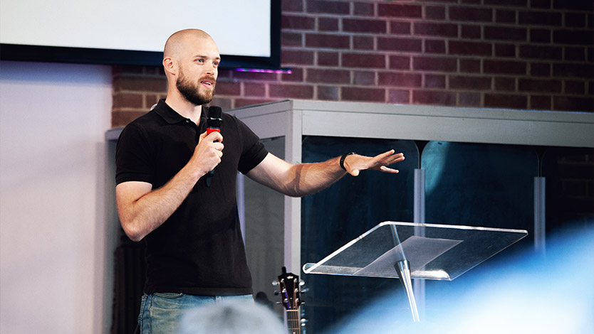 Ben Poch preaching on the stage at a Half Six at regeneration Church