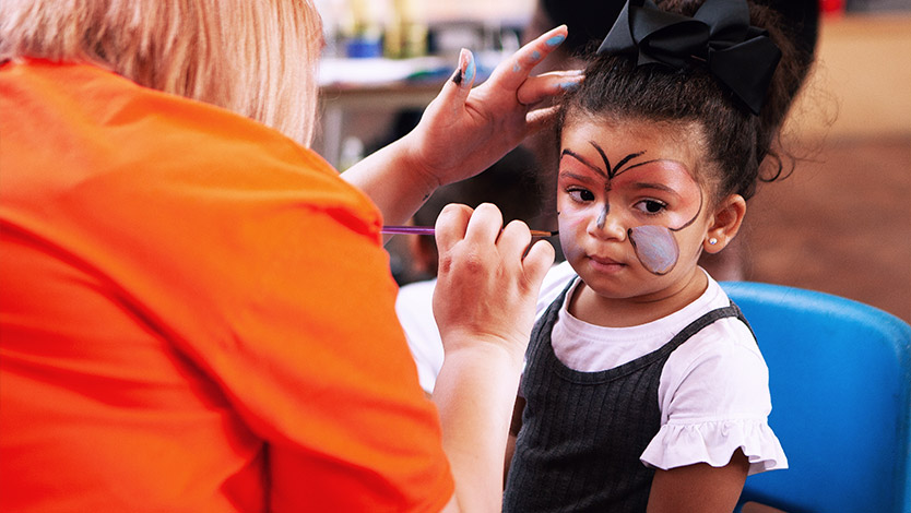 A child sitting still while have a butterfly facepainted on them by an adult during a Summer Party at Little Paws