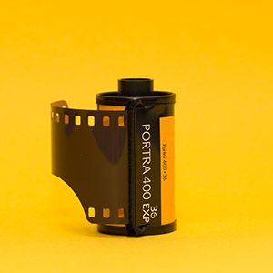 A single roll of Kodak Portra 400 film on a yellow background