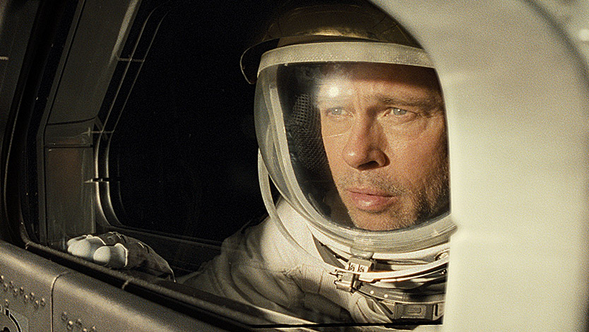 Brad Pitt in Ad Astra as an astronaut looking out of a window