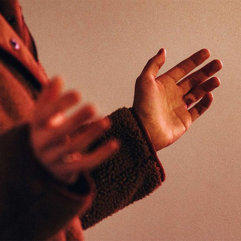 Hands reaching forwards to receive in prayer