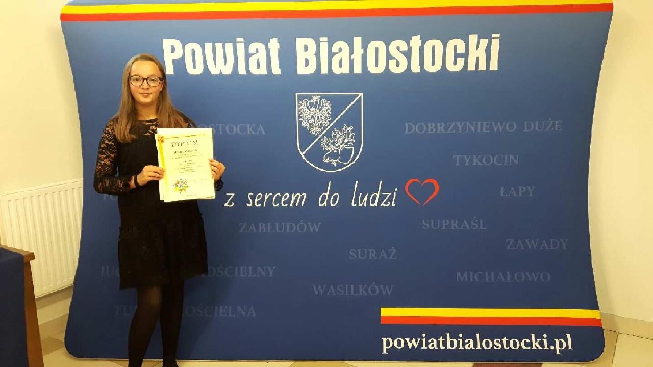 Monika z dyplomem na te niebieskiego plakatu Powiatu Białostockiego z herbem i hasłem z sercem do ludzi