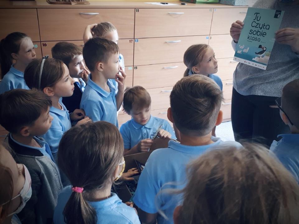 grupka dzieci, któym wychowawczyni pokazuje plakat programu Tu czyta sobie pierwsza klasa
