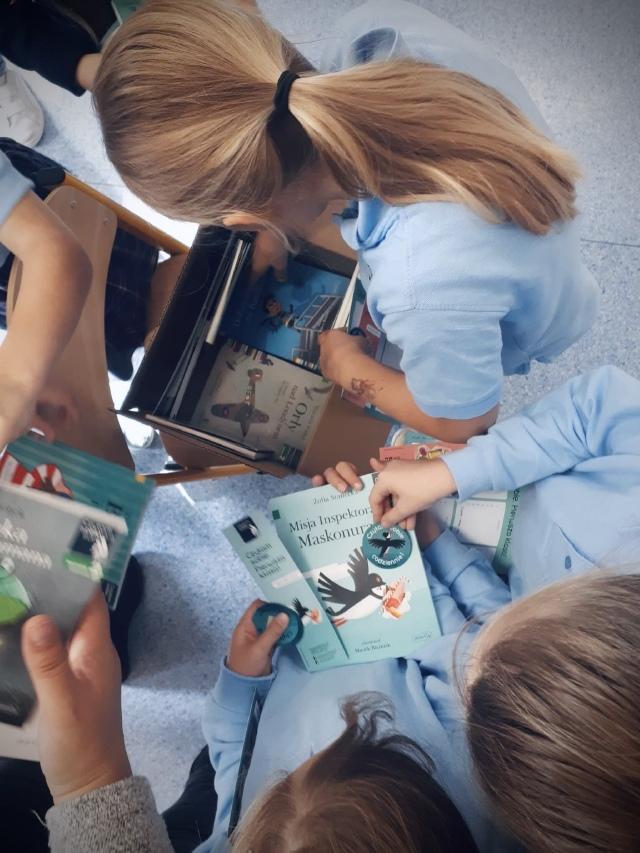 Dziewczynka pochylona nad otwartym kartonikiem z książkami