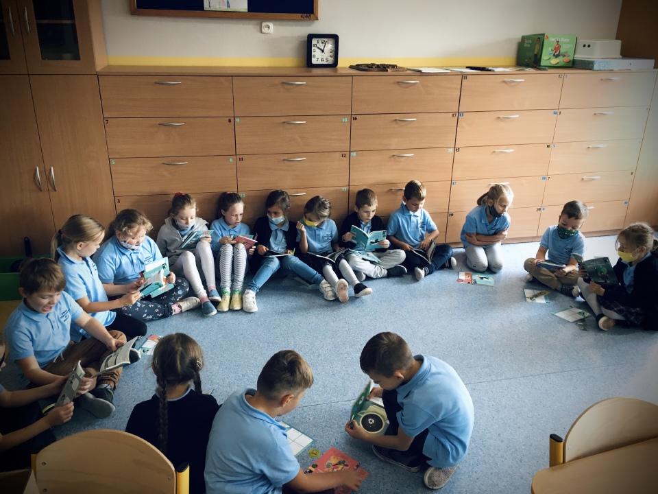 Dzieci z klasy 1 siedzą w kole i czytają lub przeglądają otrzymane książki
