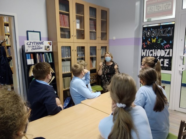 Na zdjęciu znajduje się pani Dyrektor wraz z grupą młodych chłopców i dziewcząt, słuchających tego, co mówi