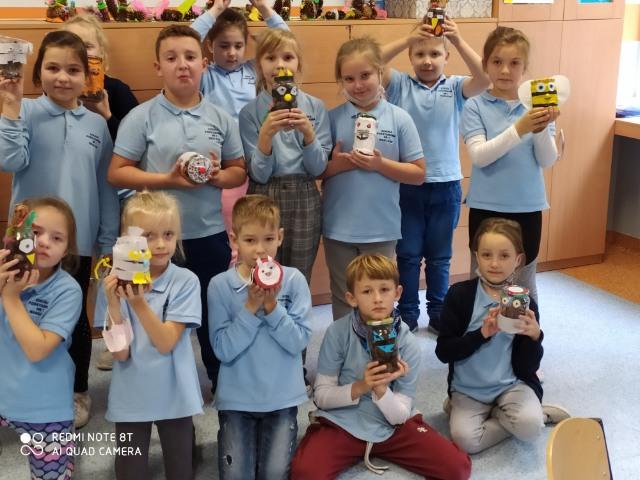 Uczniowie i uczennice z klasy 2a demonstrują wykonane przez siebie zwierzęta i owady ze słoików
